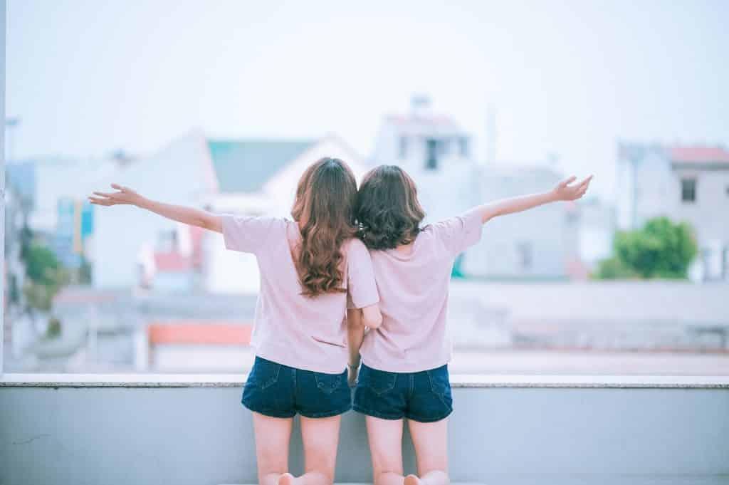 Imagem de um casal homossexual de braços dados olhando para uma rua. Elas estão felizes e de braços abertos.