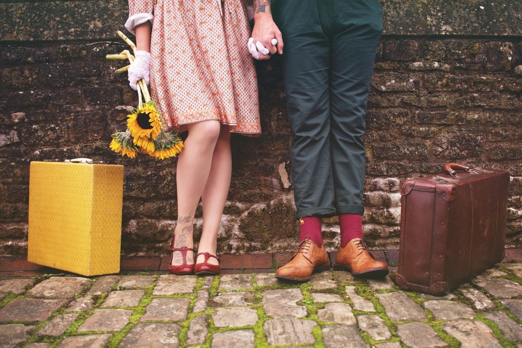 Imagem de um casal assexual. Eles estão de mãos dadas encostados em uma parede. Ela usa um lindo vestido e ele uma calça azul e meias bordô. A moça segura em uma das mãos um ramalhete de girassóis. As malas de ambos estão uma ao lado deles.