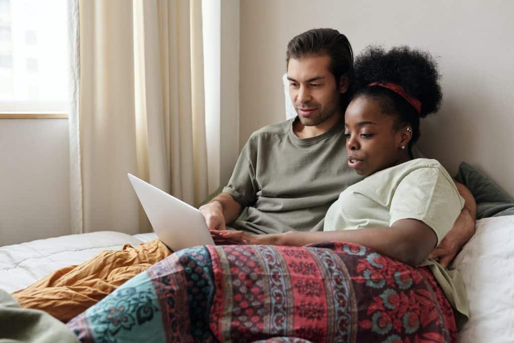 Foto de um homem e uma mulher deitados no sofá, abraçados, usando o computador.