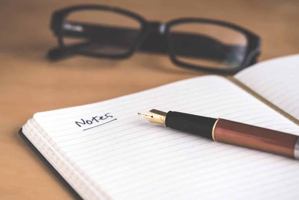 Caderno de anotações aberto com uma caneta em cima e um óculos em frente