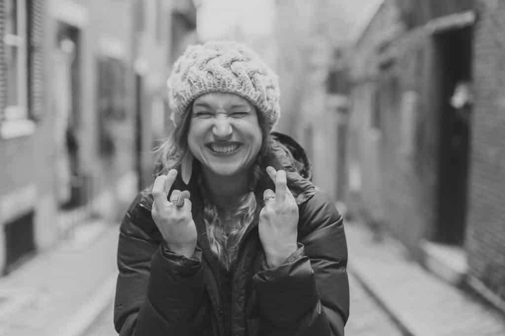 Mulher na rua sorrindo com olhos fechados fazendo figas com os dedos da mãos