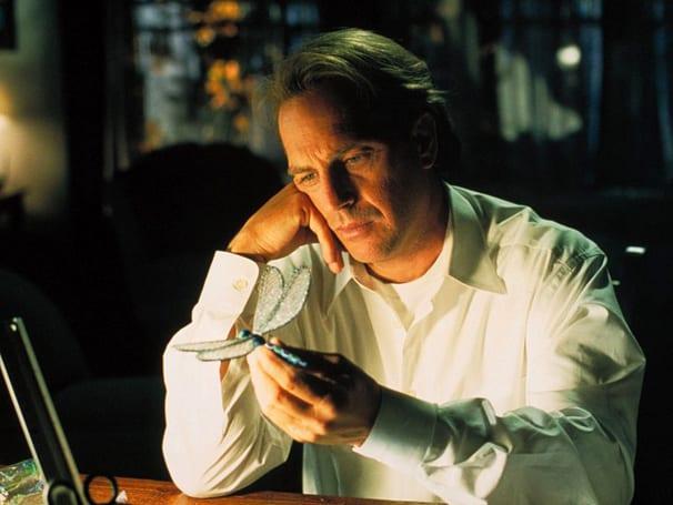 Homem em sua mesa pensativo olhando para uma libélula