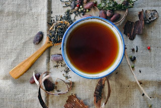 Caneca de chá vista de cima com folhas em volta e colher de madeira