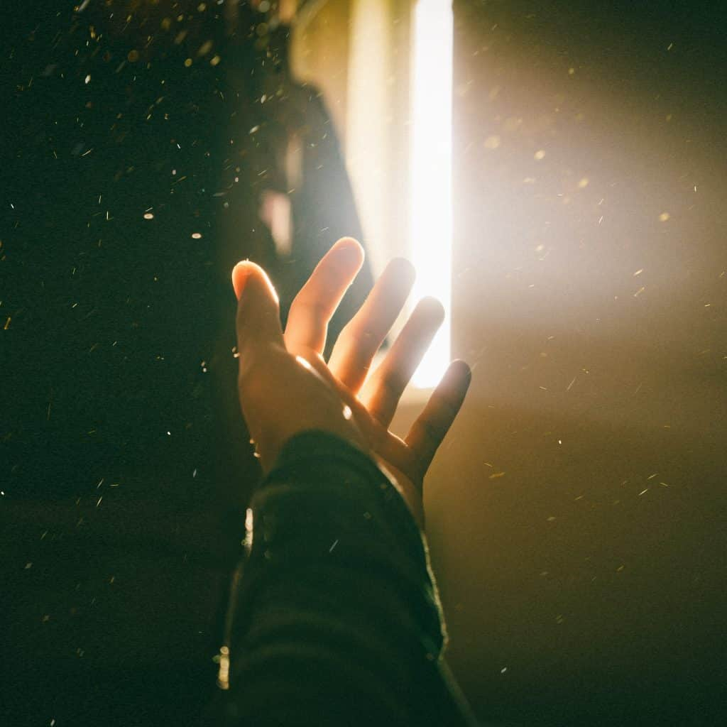 Pessoa com a mão aberta em direção a um faixo de luz da janela