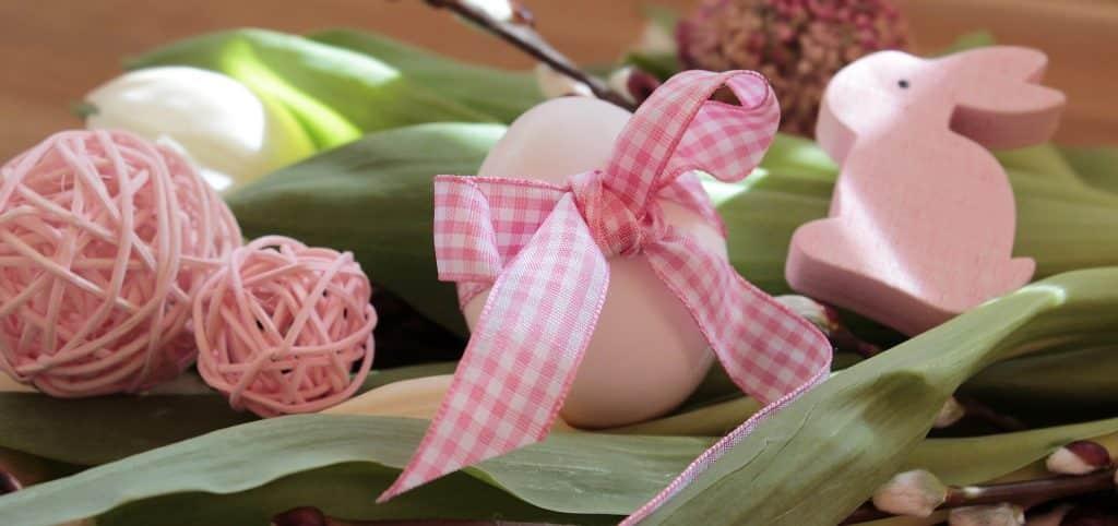 Imagem de um ovo branco com um laço cor de rosa. Ao lado a imagem de um coelhinho e uma bola de linha na cor rosa.
