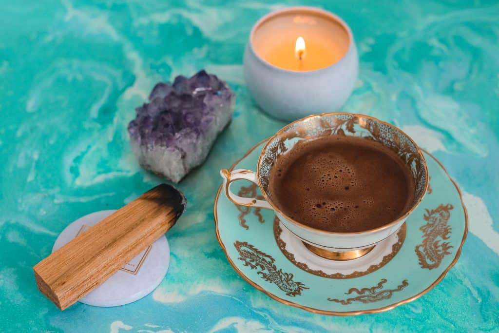 Uma xícara de chá, uma vela, um cristal e um incenso de madeira sobre uma mesa