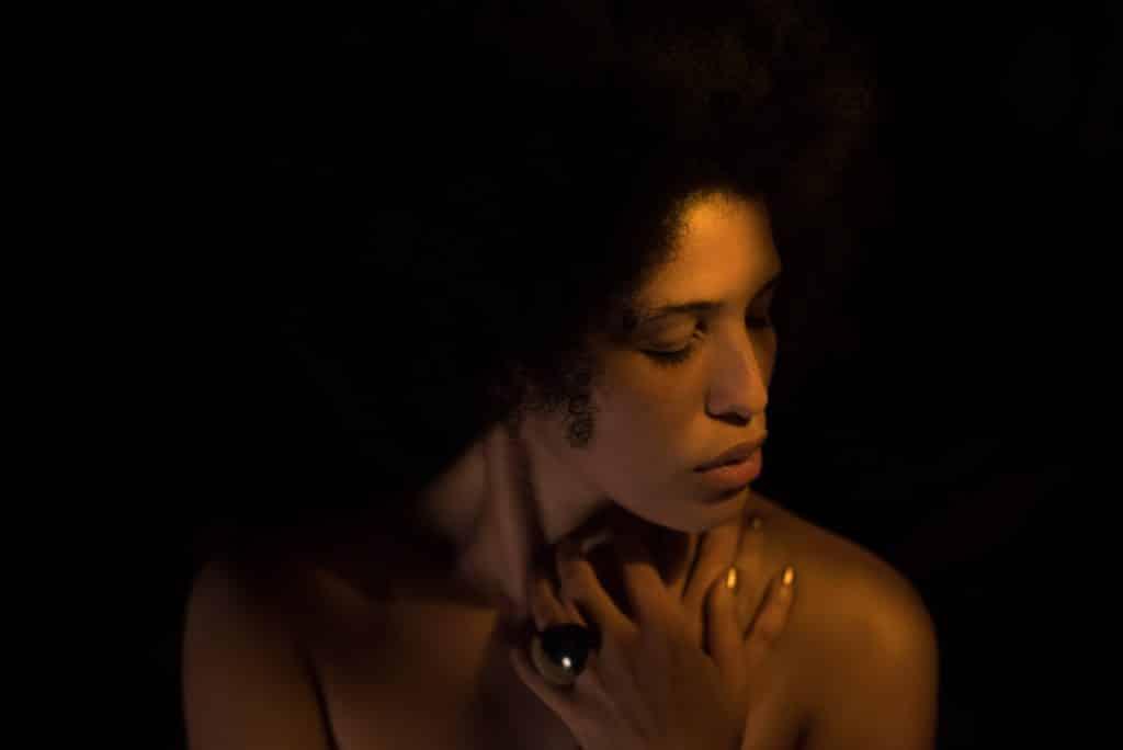 Mulher em um ambiente escuro com os olhos fechados e com suas mãos perto do pescoço e do ombro