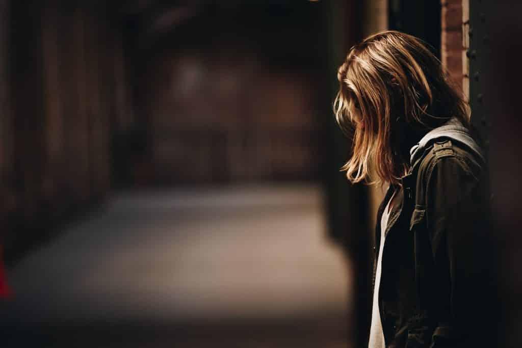 Mulher na rua encostada na parede olhando para baixo
