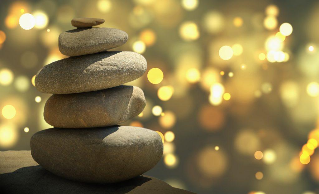 Imagem das pedras de feng shui e ao fundo muitas luzes representando a espiritualidade e a física quântica.