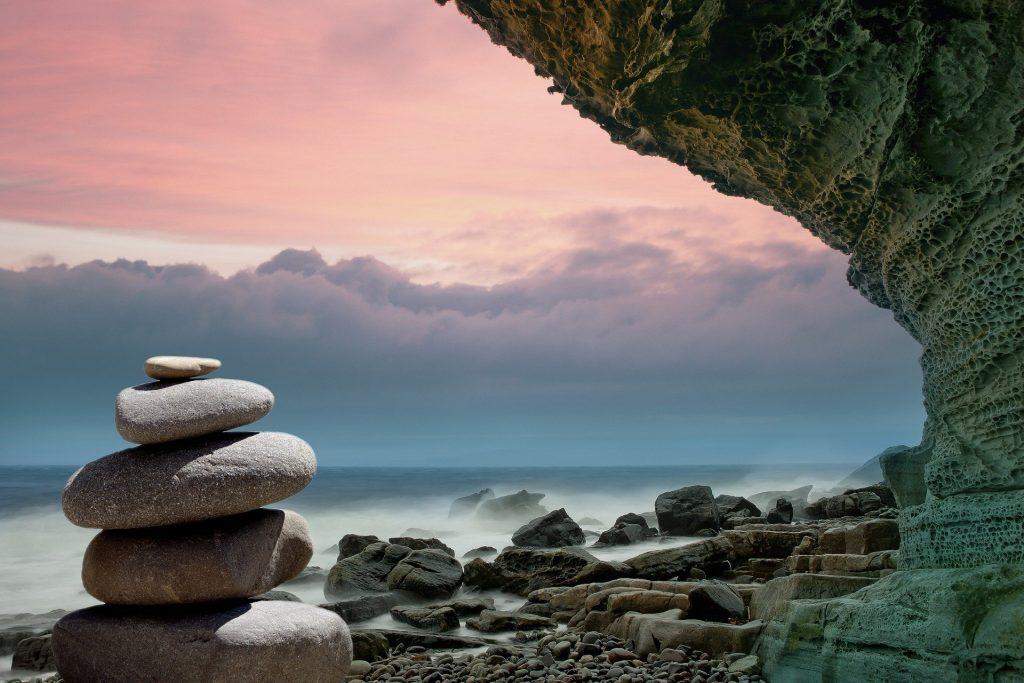 Imagem de várias pedras e uma de feng shui representando a espiritualidade e a física quântica.