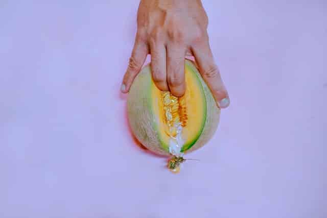 Mão apertando melão em fundo lilás