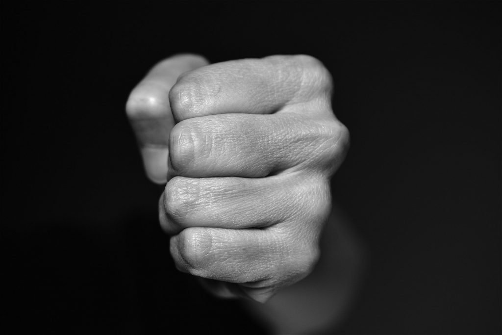 Imagem em preto e branco da mão fechada de um homem pronto para agredir.