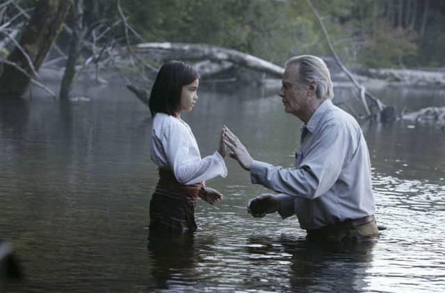 Homem e criança em um lago com as mãos próximas