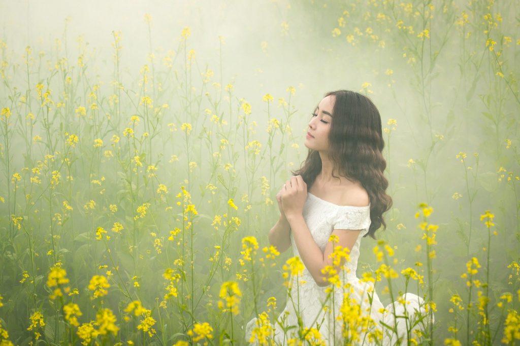 Imagem de um campo com flores amarelas em pleno nevoeira e uma mulher usando um vestido branco de renda fazendo a oração do perdão.