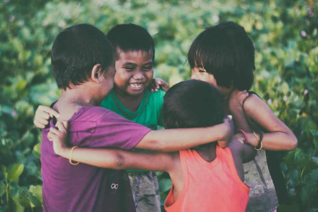 Crianças abraçadas em um círculo, rindo.