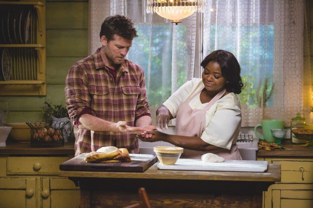Homem cozinhando com mulher ao seu lado