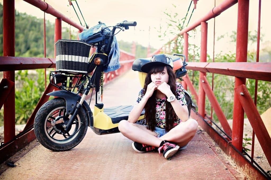 Imagem de uma ponte e sobre ela uma jovem garota que usa um boné de lado, shortes e camiseta alegre. Ela está sentada no chão e com um semblante bem despreocupado. Ao lado dela, sua mobilete.