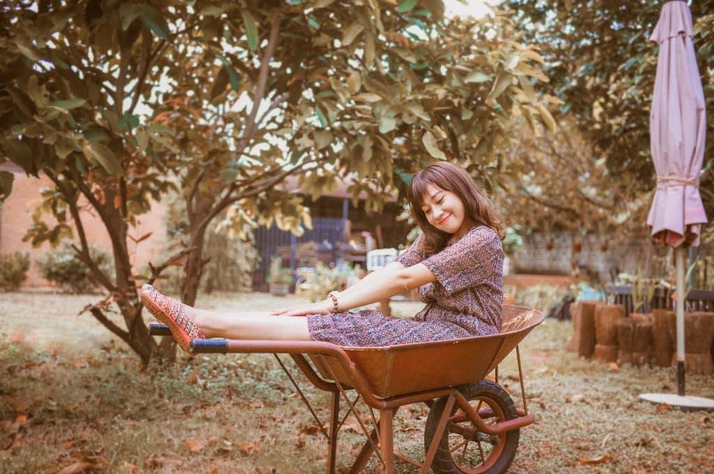 Imagem rústica de um quintal. Nele encontra-se uma garota usando um vestido rústico e ela está sentada dentro de um carrinho de mão.