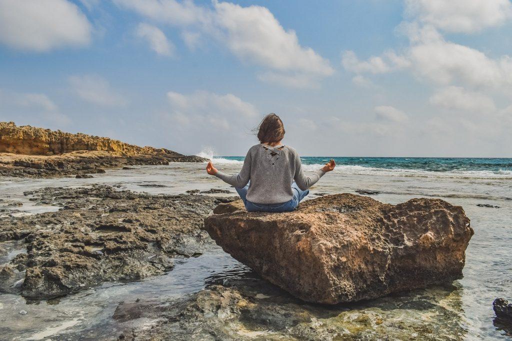Imagem de uma mulher sentada de costas em uma pedra grande próximo ao mar. Ela está em posição de meditação.