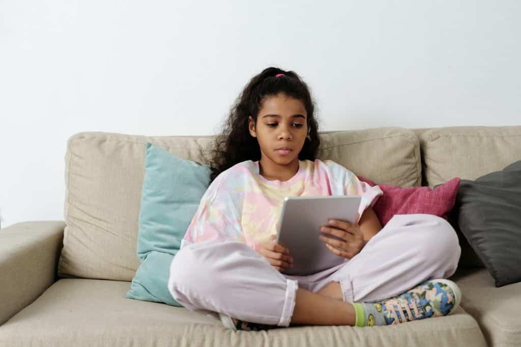 Menina sentada no sofá usando seu tablet.