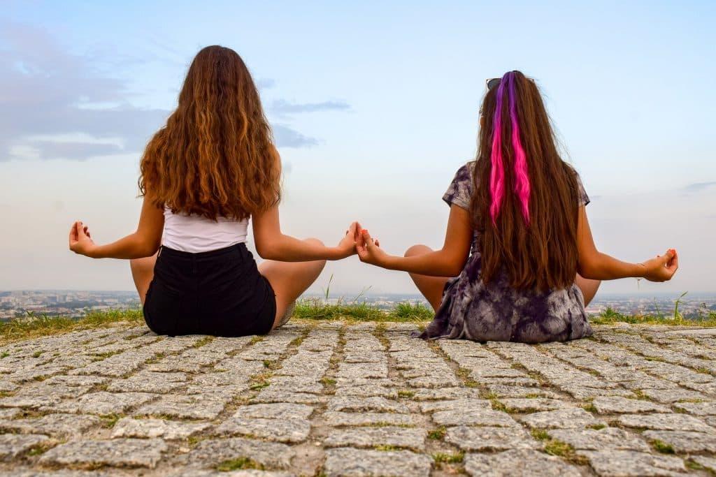 Imagem de duas garotas de costas sentadas no chão fazendo o uso da meditação.