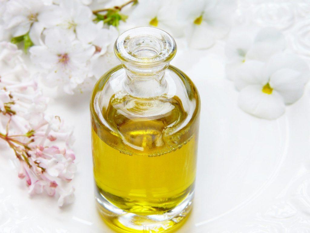 Imagem de um vidro contendo óleo de mirra. O vidro está sobre uma mesa branca decorada com flores nas cores rosa e branca.