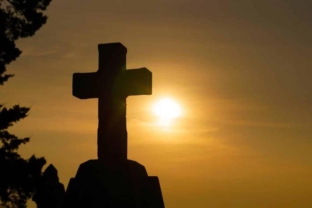 Imagem da cruz em um lugar alto. Ao fundo da imagem um lindo por do sol. A cruz representa a espiritualidade das pessoas.