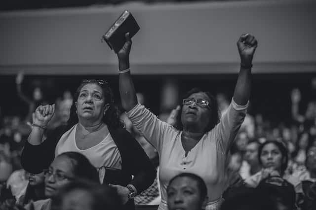 Mulheres em pé em culto com braços para o alto e bíblia na mas mãos