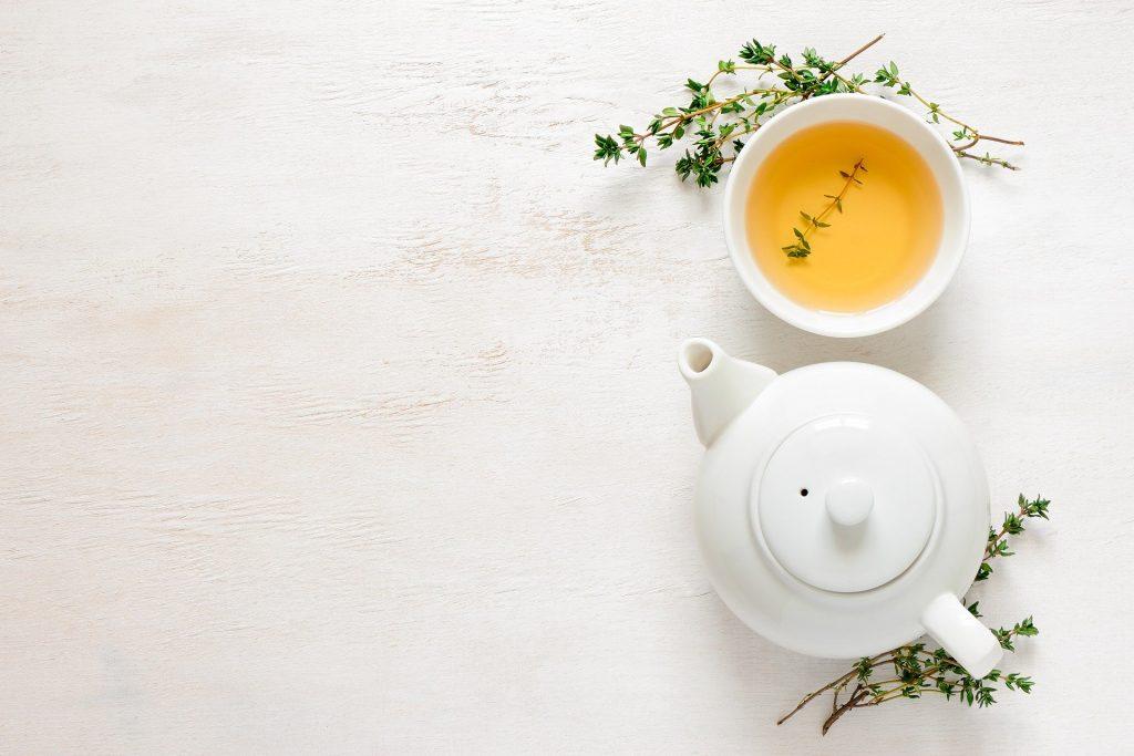 Imagem de receitas com alfavaca. A foto é de uma xícara de chá da erva e um bule feito de porcelana branca.