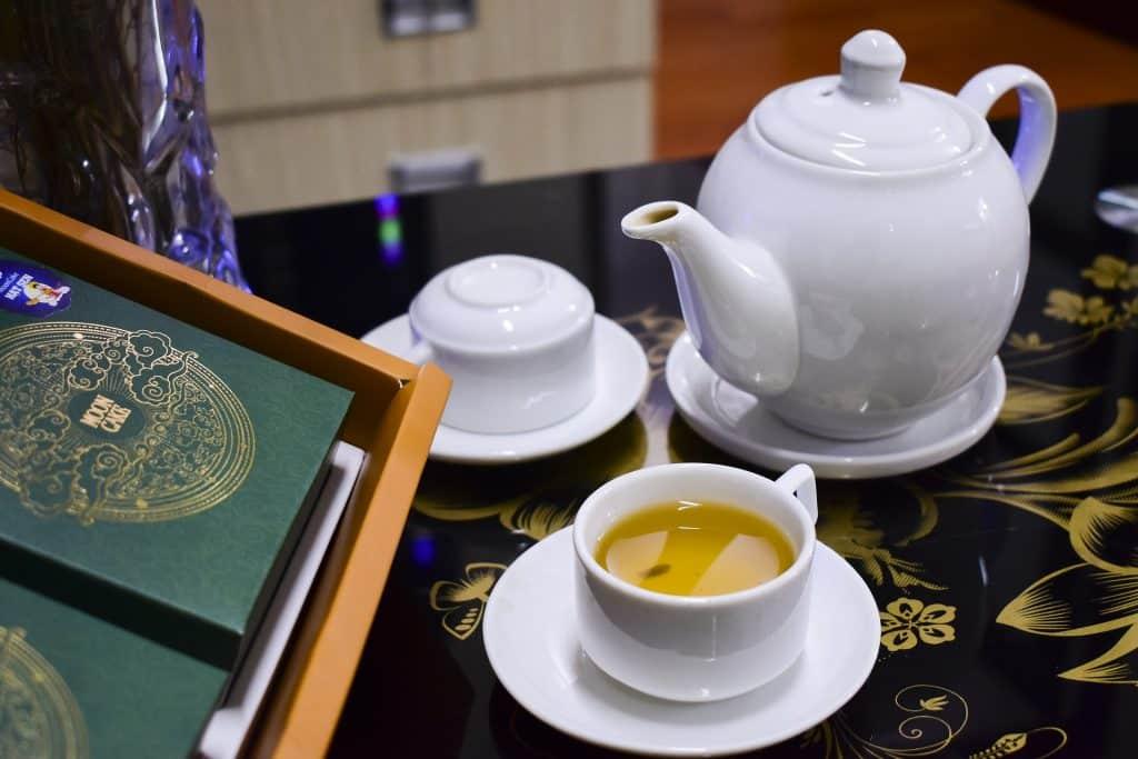 Imagem de um bule e xícaras com chá para dor de estômago e fígado servidos sobre uma mesa azul desenhada com flores douradas.