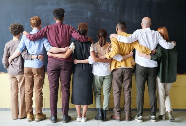 Pessoas em pé de costas com braços dados representando diversidade