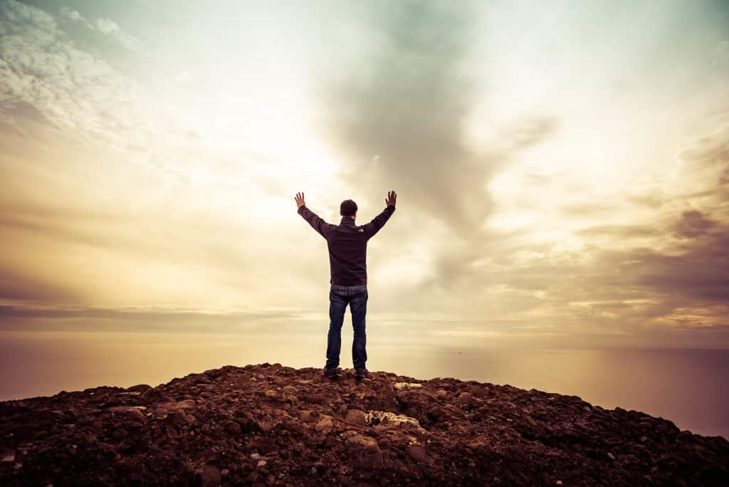 Homem no topo de uma montanha com os braços abertos em direção ao céu