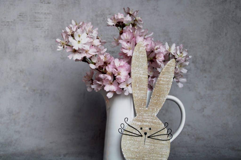 Imagem de um lindo vaso branco de porcelana cheio de flores na cor rosa. Ao lado a fprma da carinha do coelho da Páscoa.