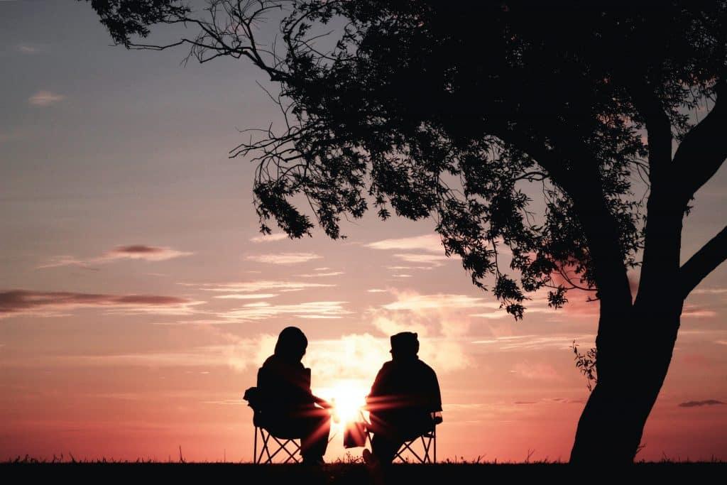 Duas pessoas conversando ao lado de uma árvore olhando o pôr do sol