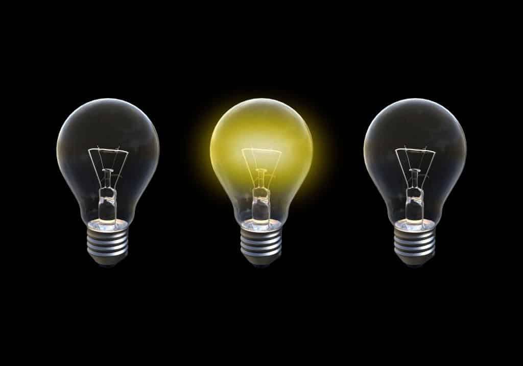 Imagem de fundo preto com três lâmpadas, sendo que a do meio está acesa. A lâmpada representa a solução para um problema, o significado de epifania,