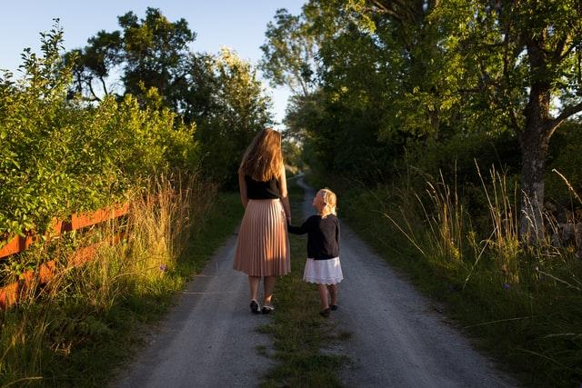 Mãe e filha de mãos dadas andando de costas em estrada no meio de árvores