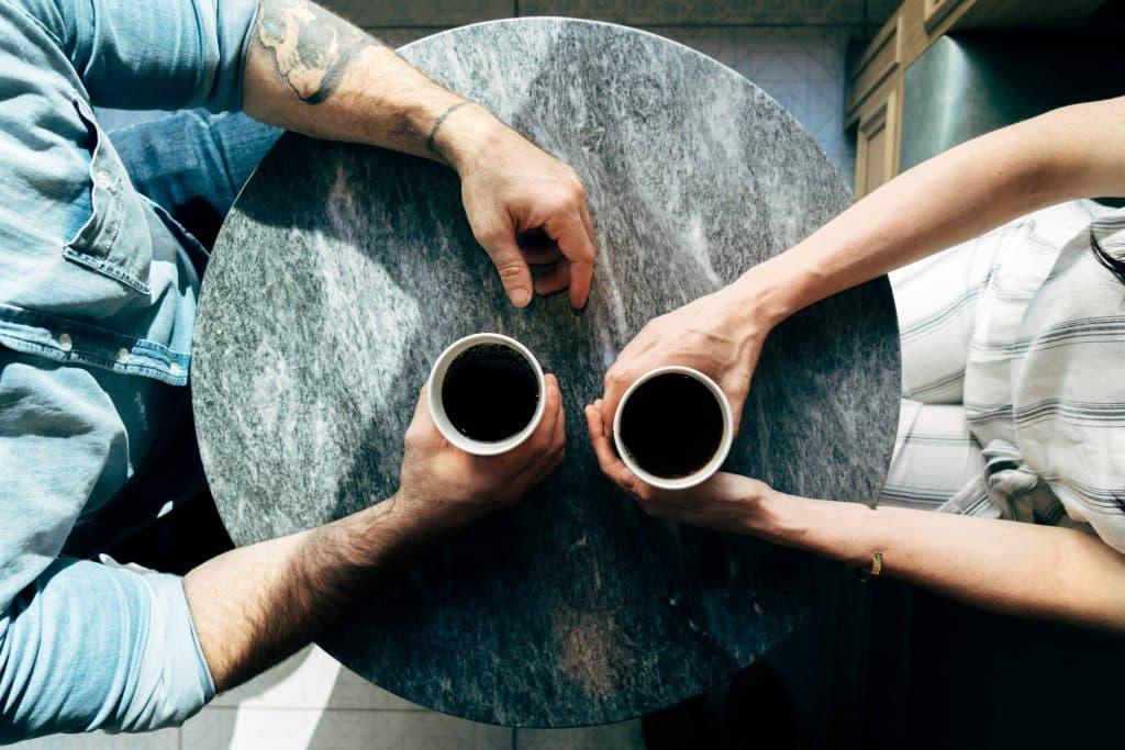 Duas pessoas conversando sentadas segurando xícara de café