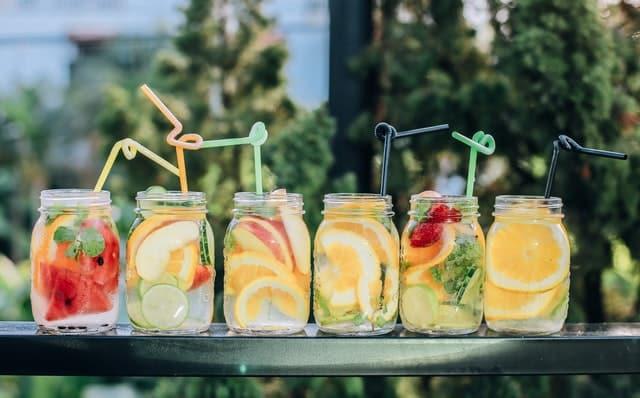 Copos de suco com frutas e canudos coloridos