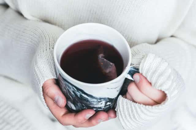 Mãos segurando xícara de chá vista de cima
