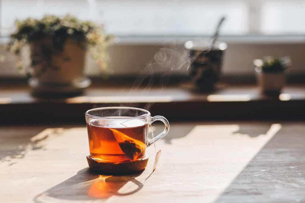 Imagem de chá para dor de estômago e fígado em infusão e servido em uma xícara de vidro.