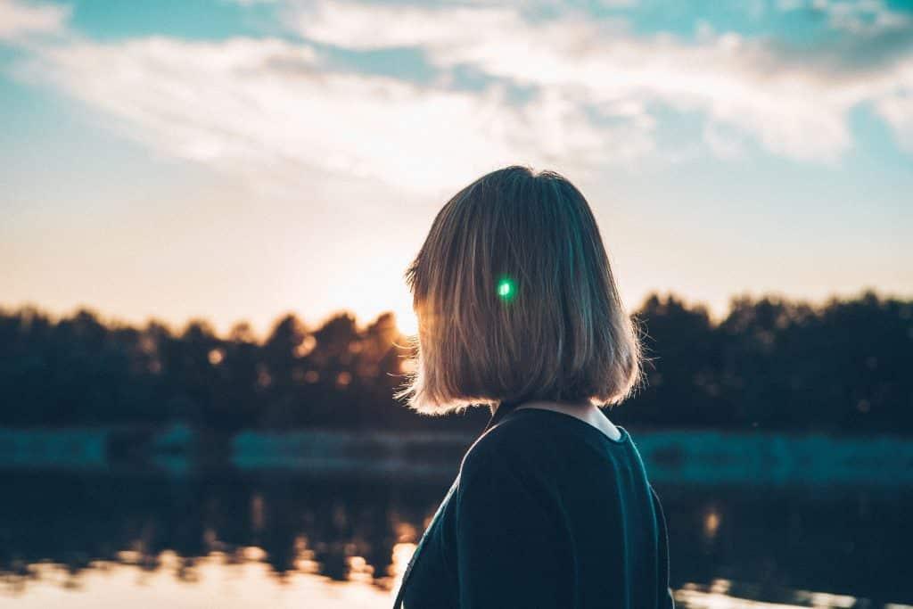 Mulher olhando em direção ao lado e ao sol
