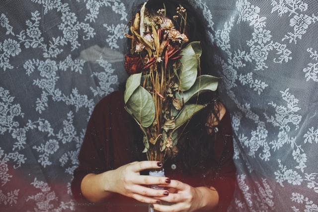 Mulher em pano transparente segurando flores em frente ao rosto