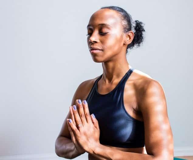 Mulher com mãos em frente ao corpo unidas e olhos fechados meditando