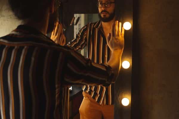 Homem em frente a espelho com mãos apoiadas visto de costas