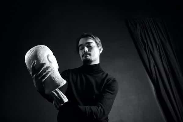 Homem de olhos fechados segurando cabeça de estátua em foto preta e branca