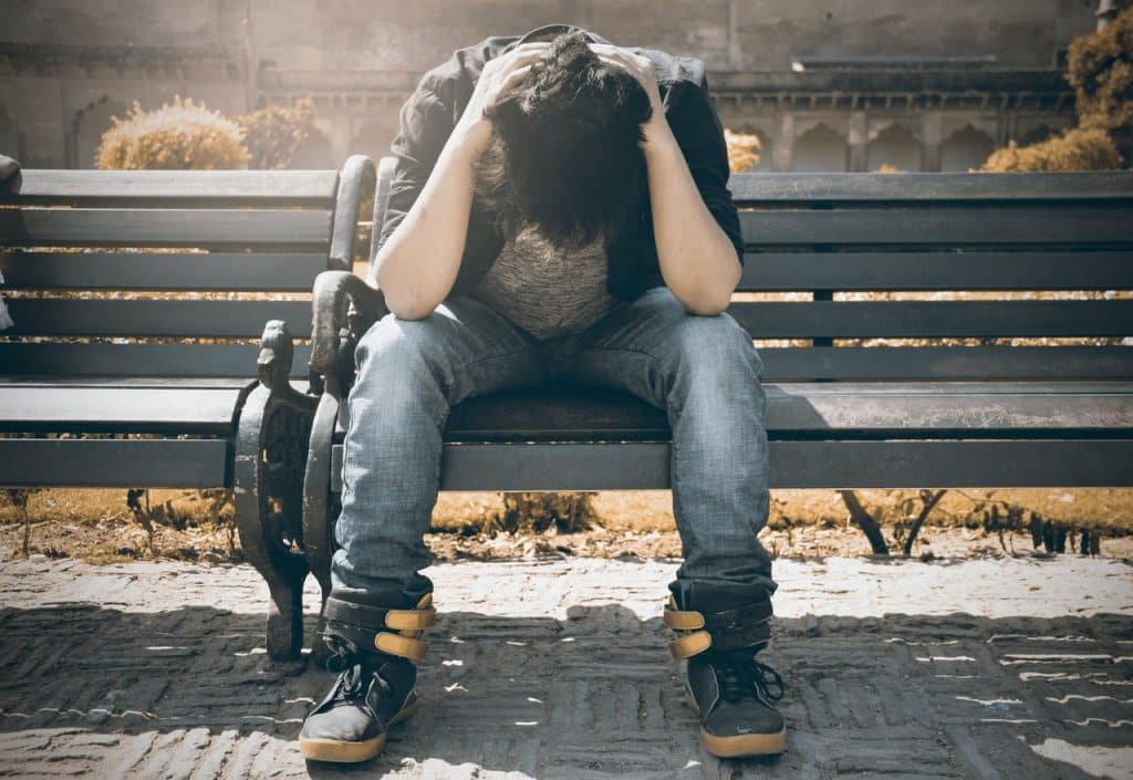 Homem sentado em banco público. Sua cabeça está baixa, e suas mãos estão em sua nuca.