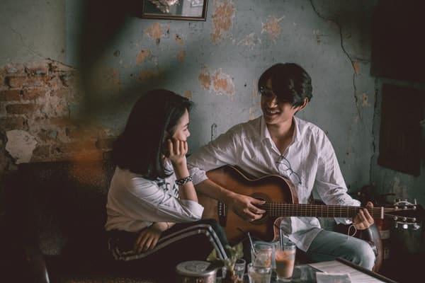 Casal em sala de casa com homem tocando violão e mulher cantando