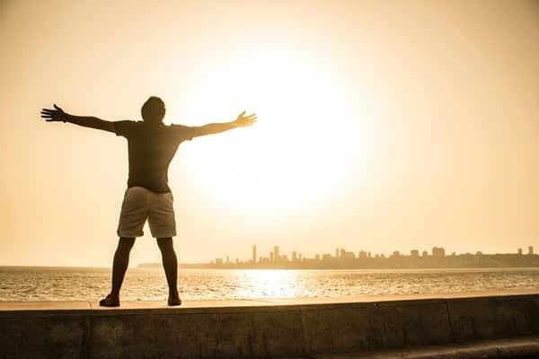 Homem em parapeito com braços abertos e mar a frente com sol refletindo