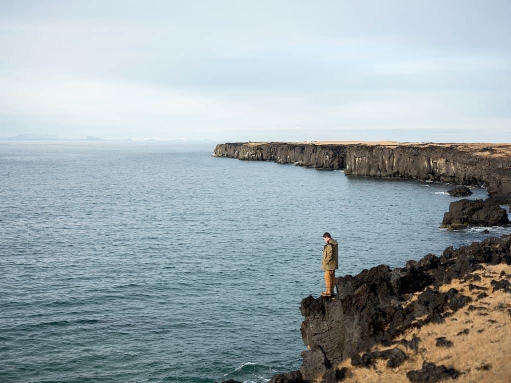 Homem em pé sobre uma rocha, em frente ao mar.
