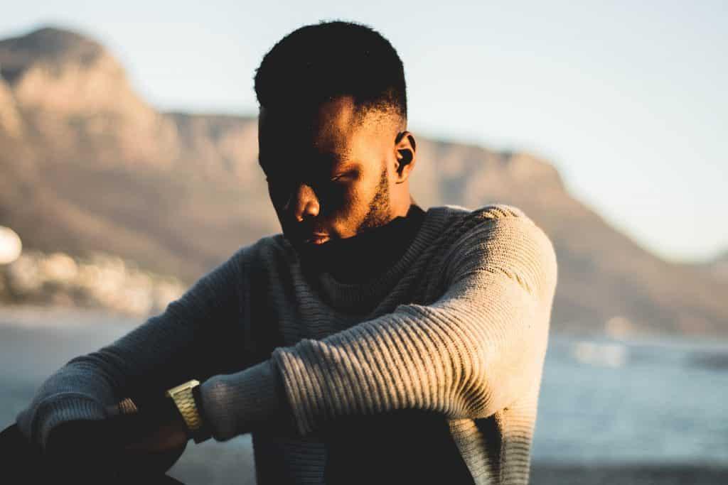 Homem de suéter sentado em frente a uma paisagem com um rio e montanhas.
